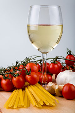 cherry tomatoes, garlic cloves, pasta, and a glass of white wine